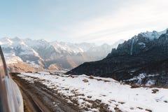 Eine Ansicht von der SUV-` s Fahrer ` s Tür zu einer Landschaftslandstraße mit Schmutz und einem Tal von Bergen im Abstand Stockbilder