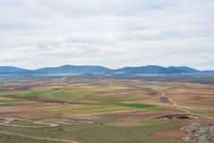 Eine Ansicht von einem Hügel zu den Feldern, zu den Bauernhöfen und zu den Bergen Stockbild