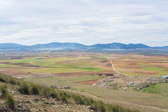 Eine Ansicht von einem Hügel zu den Feldern, zu den Bauernhöfen und zu den Bergen nahe Consuegra Lizenzfreie Stockfotos