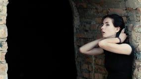 Eine Ansicht von links zu righ einer jungen Frau, lehnend an einer Wand, seufzen und bringen ihr Haar durcheinander stock video