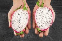 Eine Ansicht von oben genanntem auf einer bunten Drachefrucht in den männlichen Händen eine tropische Frucht auf einem grauen Ste stockbild