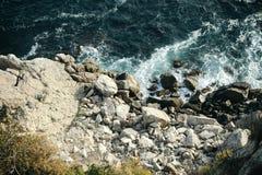 Eine Ansicht von oben genanntem von den Meereswellen und von Felsen, die auf dem Ufer rollen Lizenzfreies Stockbild