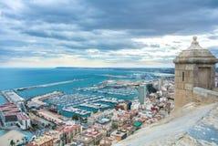 Eine Ansicht von Santa Barbara Castle am Hügel in der Mitte von Alicante zu einem Hafen der Stadt mit einem viel von Yachten Stockfotografie