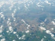Eine Ansicht von Wolken und von Feldern von einem Flugzeug stockfotografie