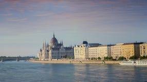 Eine Ansicht, welche die Stadt des ungarischen Parlaments-Gebäudes und des Budapests und des Flusses Donau bei rosa Sonnenunterga Stockfotos