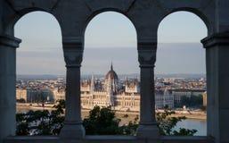 Eine Ansicht, welche die Stadt des ungarischen Parlaments-Gebäudes und des Budapests und des Flusses Donau bei rosa Sonnenunterga Stockbild