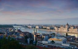 Eine Ansicht, welche die Stadt des ungarischen Parlaments-Gebäudes und des Budapests und des Flusses Donau bei rosa Sonnenunterga Stockfotografie