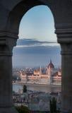 Eine Ansicht, welche die Stadt des ungarischen Parlaments-Gebäudes und des Budapests und des Flusses Donau bei rosa Sonnenunterga Stockfoto