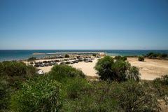 Eine Ansicht zum geheimen Paradiesstrand und Jachthafen in einem heißen Sommer weekend, Zypern Lizenzfreies Stockfoto