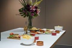 Eine Anzeige einer Käseservierplatte mit einem klaren Vase Blumen lizenzfreie stockbilder