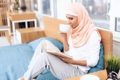 Eine arabische Frau trinkt Tee und liest ein Buch beim Sitzen auf dem Bett stockfotos