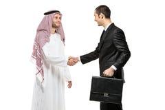 Eine arabische Person, die Hände mit einem Geschäftsmann rüttelt Stockfoto