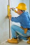 Eine Arbeitskraft, die auf Betonmauer überlagert stockbild