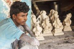 Eine Arbeitskraft, die vor Ganesh-Idolen sitzt Stockbild