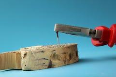 Eine Arbeitskraft entfernen Rostnagel mit Helferkombinationszangen Manuelle harte Arbeit lizenzfreie stockfotos