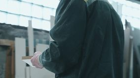 Eine Arbeitskraft mit Gläsern sägt Material in der Produktion und Blicke am Ergebnis stock video footage