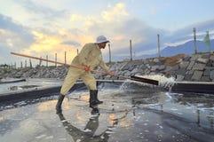 Eine Arbeitskraft schlägt Wasser aus dem Salz heraus, das am frühen Morgen Feld extrahiert Stockfotos