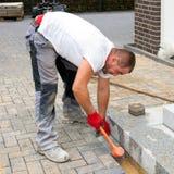 Eine Arbeitskraft stellt eine Terrasse von konkreten Pflastersteinen her Lizenzfreies Stockfoto