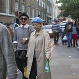 Eine Asiatin in einem Blauhelm und in einem Regenmantel mit einem chinesischen Mann in einem Hut und in der Sonnenbrille gehend a Lizenzfreies Stockbild