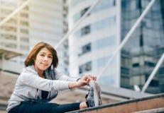 Eine Asiatin wärmt sich, um in einer Großstadt zu trainieren heal stockfotografie