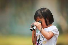 Eine asiatische Anwendung des kleinen Mädchens Ferngläser durch ihre Selbst Stockfotos