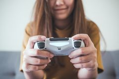 Eine asiatische Frau, die den Gamecontroller beim Spielen von Spielen mit glaubendem Spaß und glücklich hält stockfotografie