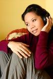 Eine asiatische Frau, die ihre Lieblingsmusik genießt Stockbilder