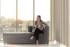 Eine asiatische langhaarige Frau ist das Sitzen im Schneidersitz auf dem Sofa s lizenzfreies stockbild