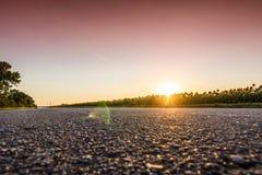 Eine Asphaltstraße auf dem Hintergrund des purpurroten Sonnenuntergangs Lizenzfreie Stockbilder