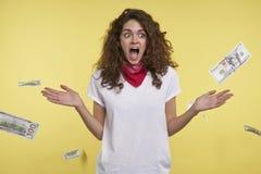 Eine Atelieraufnahme der Frau, die viel Geld gewinnt, Bargeld, das auf ihren Kopf, lokalisiert über gelbem Hintergrund fällt stockfoto