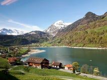 Eine atemberaubende Schneegebirgs- u. -seedorfansicht entlang den szenischen Zugweg in der Schweiz Stockbilder