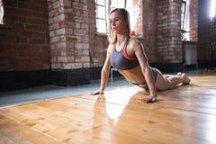 Eine Athletenfrau, die auf Training aufw?rmt Ausführung von gesunden Übungen für die Rückseite und den Dorn lizenzfreie stockfotos