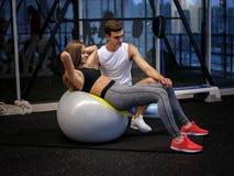 Eine athletische Frau in der sportlichen Kleidung, die Übungen auf einem Eignungsball auf einem Turnhallenhintergrund tut Diät, g Lizenzfreie Stockfotos