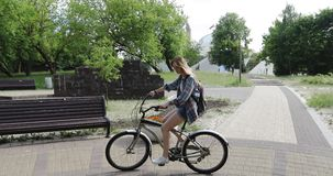 Eine attraktive Blondine fährt herum in einen Park im Sommer rad stock footage