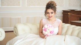 Eine attraktive Braut der jungen Frau mit einem Blumenstrauß von Blumen sitzt auf der Couch in einem luxuriösen Raum Sie wartet stock footage