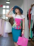 Eine attraktive Dame in einem Blau Eber-geströmten Hut schließt Käufe auf einem Kleidungsshophintergrund ab Verkaufs- und Modekon Stockfotografie