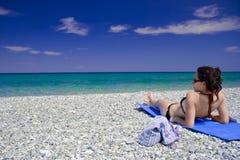 Eine attraktive Frau, die auf dem Strand liegt lizenzfreie stockfotografie