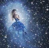 Eine attraktive Frau in einem blauen Kleid auf einem schneebedeckten Hintergrund Stockbild