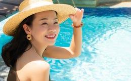 Eine attraktive Frau sitzt durch das Pool lizenzfreie stockfotos