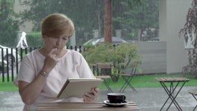 Eine attraktive Greisin mit einer Tasse Tee das Lesung und Schreiben auf einer Tablette in der Terrasse stock video