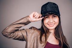 Eine attraktive junge Brunettefrau in einer Baseballmütze mit einem Lächeln, welches die Kamera betrachtet Emotionales Gesicht, G lizenzfreie stockfotos