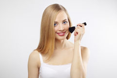 Eine attraktive junge Dame, die Blusher anwendet stockbild