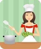 Eine attraktive junge Dame, die in der Küche kocht lizenzfreie abbildung