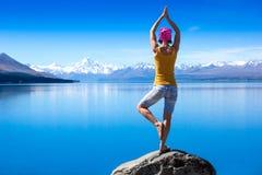 Eine attraktive junge Frau, die eine Yogahaltung für Balance tut und nahe dem See ausdehnt