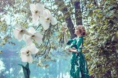 Eine attraktive junge Frau in einem Kleid des langen Grüns steht auf der Flussbank nahe bei weißen riesigen künstlichen Orchideen stockfoto