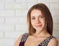 Eine attraktive junge Frau gegen eine Backsteinmauer. stockfotografie