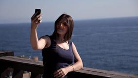 Eine attraktive junge Frau unter Verwendung eines Smartphone am Balkon eines Badekurorthotels, eine Frau fotografiert einen Sonne stock video