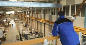 Eine Aufsichtskraft oder eine Arbeitskraft übersieht Produktion einer großen Fabrik stock video footage