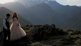 Eine ausgezeichnete Braut und ein Bräutigam vor dem hintergrund der majestätischen Berge im Sommer bei Sonnenuntergang georgia E stock footage