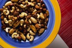 Eine Auswahl von organischen Nüssen auf bunter Platte stockfoto